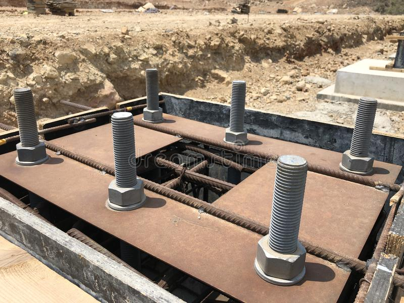Formwork and reinforcement of concrete foundation with metal anchor bolts designed for the installation of metal columns. Formwork and reinforcement of concrete stock images
