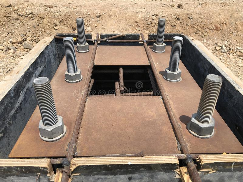 Formwork and reinforcement of concrete foundation with metal anchor bolts designed for the installation of metal columns. Formwork and reinforcement of concrete royalty free stock image