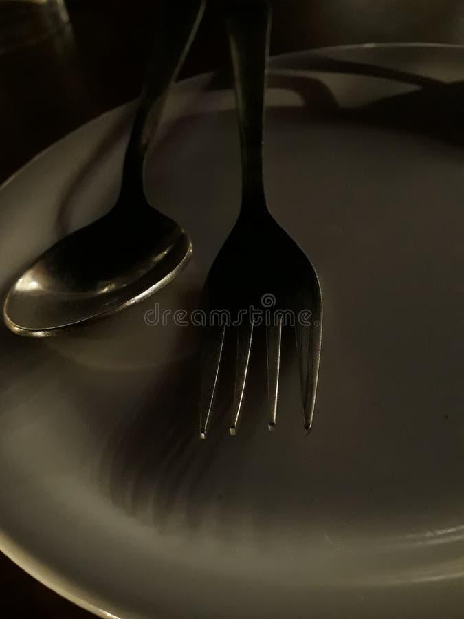 Forn och sked i den vita matställeplattan royaltyfri fotografi