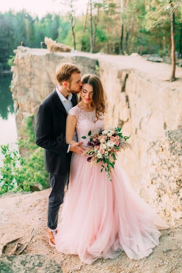 Fornal całuje jego panny młodej Szczęśliwy nowożeńcy obejmować Mężczyzna w smokingu i kobiecie w różowej ślubnej sukni pozuje dal obrazy royalty free