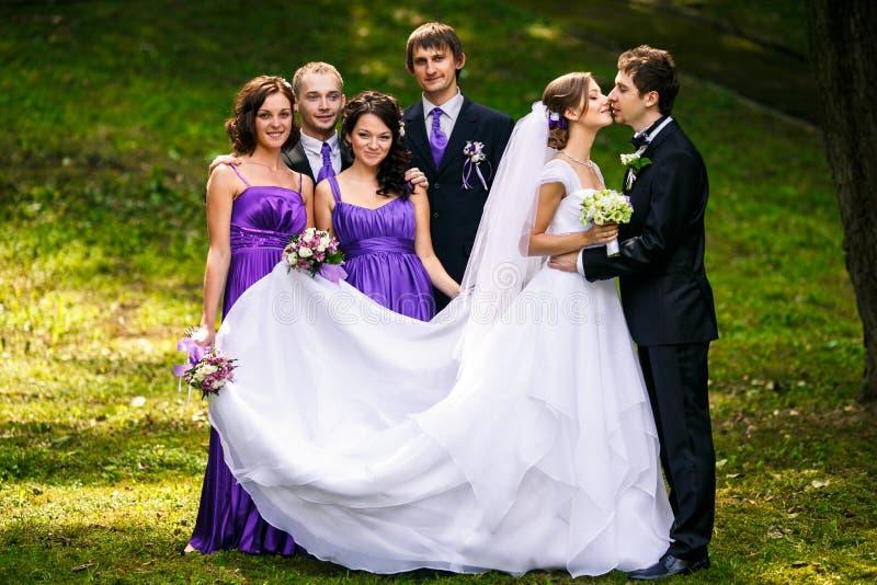 Fornal całuje panny młodej podczas gdy jego przyjaciół grymasy za on fotografia stock