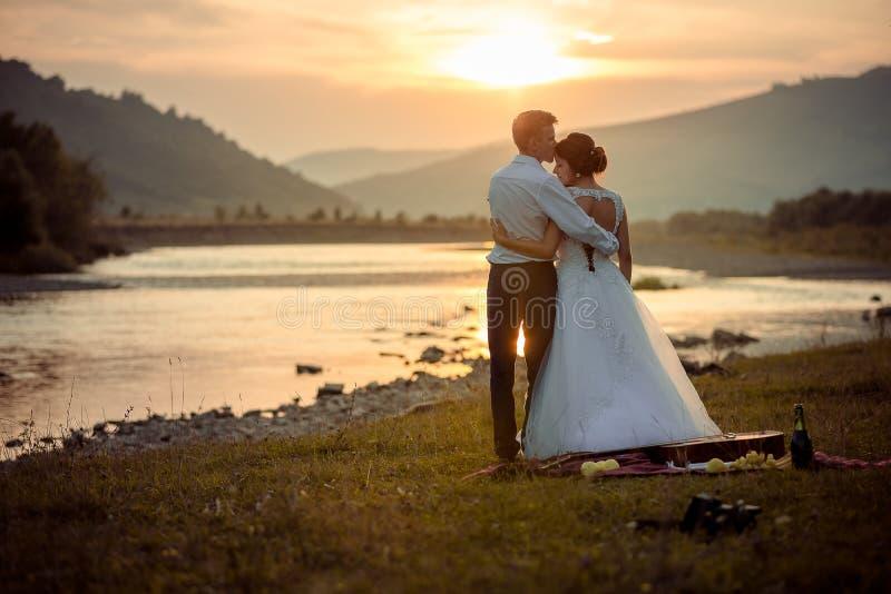 Fornal delikatnie całuje jego wspaniałej panny młodej w czole podczas zmierzchu Ślubny pinkin na brzeg rzeki zdjęcia stock