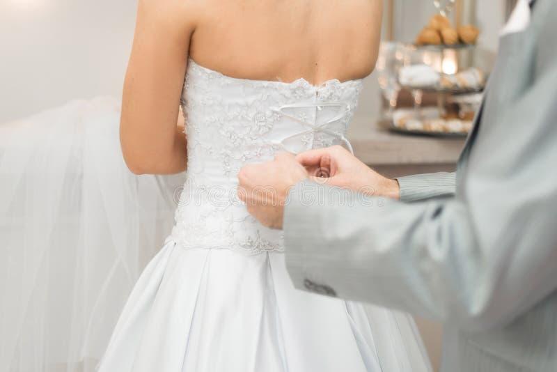 Fornal pomaga jego panny młodej wiązać koronki na ślubnej sukni zdjęcia stock