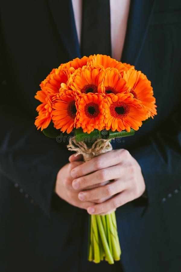 Fornal w błękitnego kostiumu mienia ślubnym bukiecie kwiaty w rękach fotografia royalty free