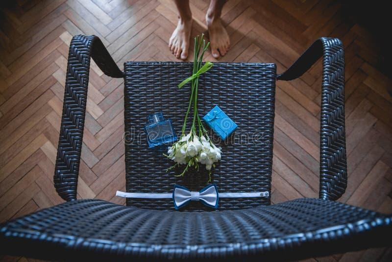 Fornal zbiera w ranku Ślubny bukiet, chusteczka motyl i prezenta pudełko na krześle, _ zdjęcie royalty free