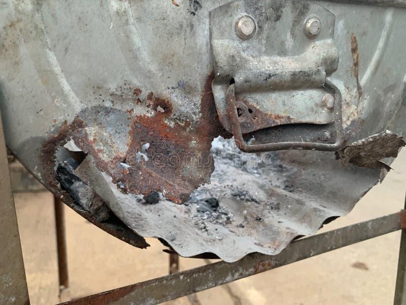 A fornalha da repreensão do zinco corroeu-se Cinza cinzenta da cinza no fogão do carvão vegetal foto de stock