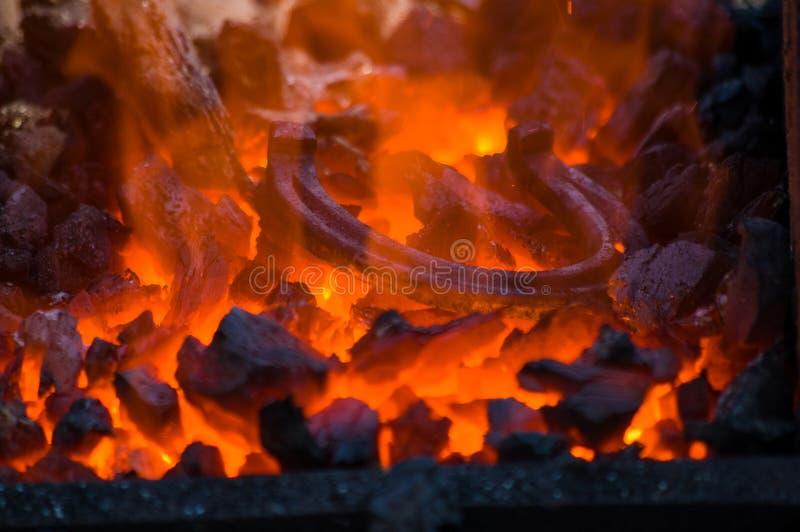Fornalha do ferreiro com carv?es ardentes, ferramentas, e a ferradura quente de incandesc?ncia fotografia de stock