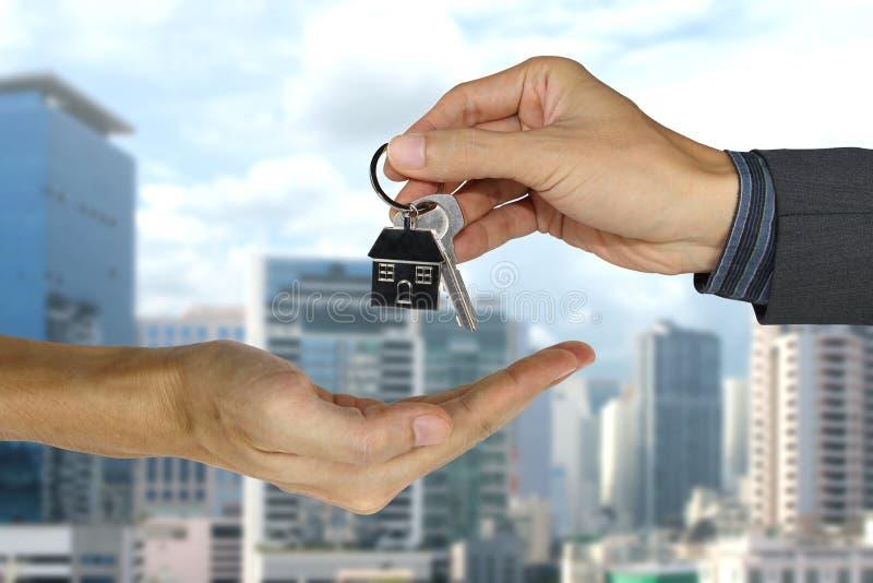 Fornendo le chiavi della casa ai clienti, al concetto della proprietà, all'ipoteca ed al concetto dell'agente immagini stock