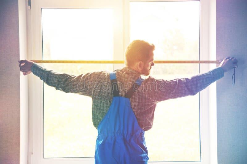 Fornisca un servizio all'uomo vicino alla finestra con nastro adesivo della misura immagini stock