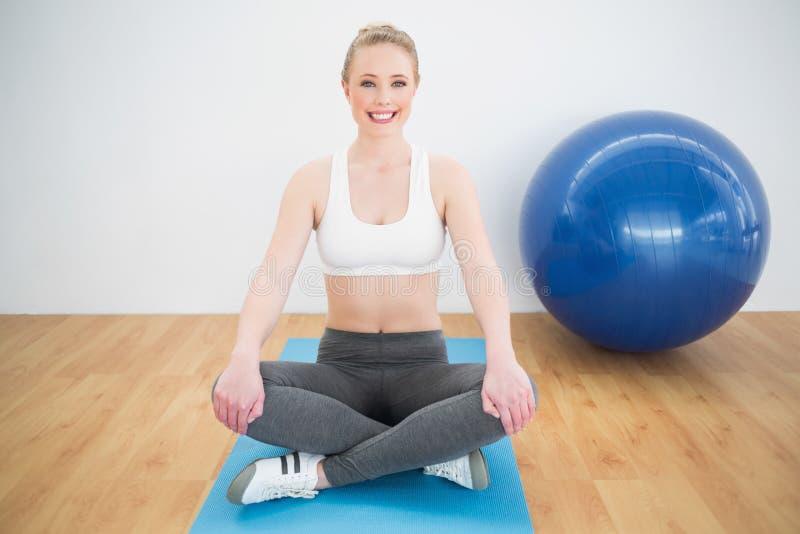 Fornito di gambe trasversale di seduta biondo sportivo sorridente sulla stuoia di esercizio fotografia stock libera da diritti
