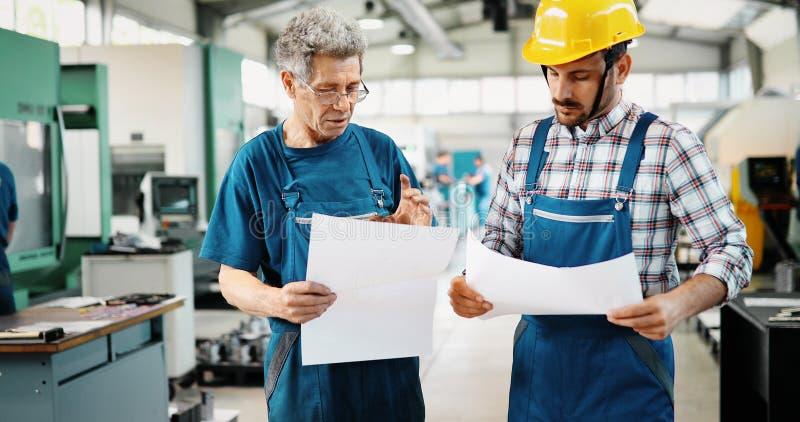 Fornitore con l'ingegnere che verifica la produzione in fabbrica immagine stock libera da diritti