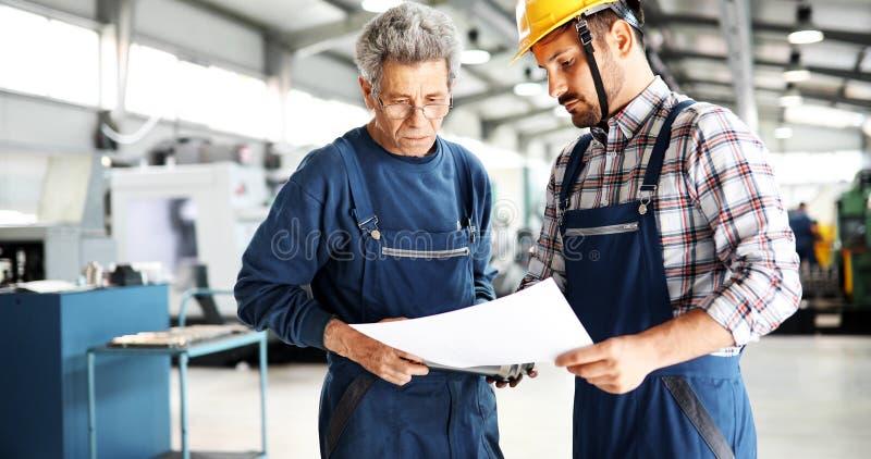 Fornitore con l'ingegnere che verifica la produzione in fabbrica fotografia stock
