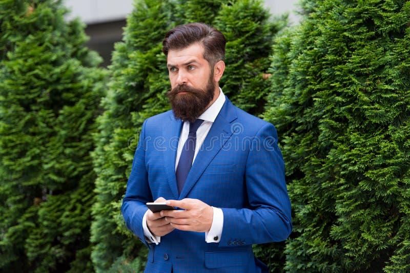 Fornitura delle risposte Uomo d'affari serio con lo smartphone Affare agile uomo barbuto sulla riunione d'affari Facendo uso di m fotografia stock libera da diritti
