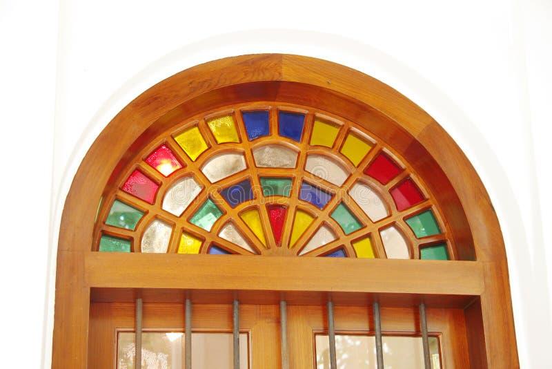 Forntida arabiskt planlagt kulört exponeringsglas välva sig ovanför dörren royaltyfri foto