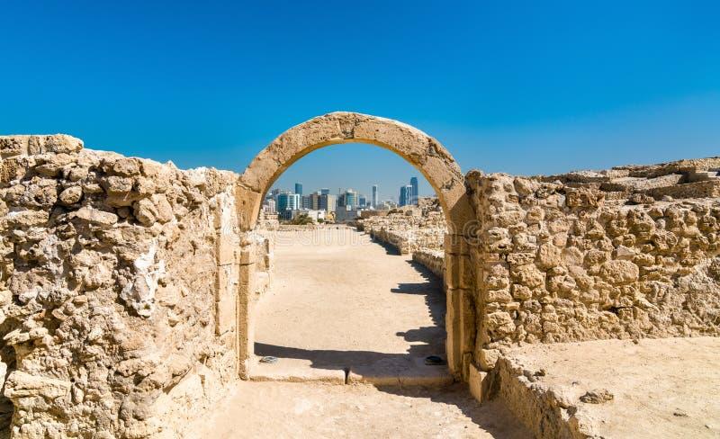 Forntida båge på det Bahrain fortet med horisont av Manama En plats för UNESCO-världsarv arkivfoton