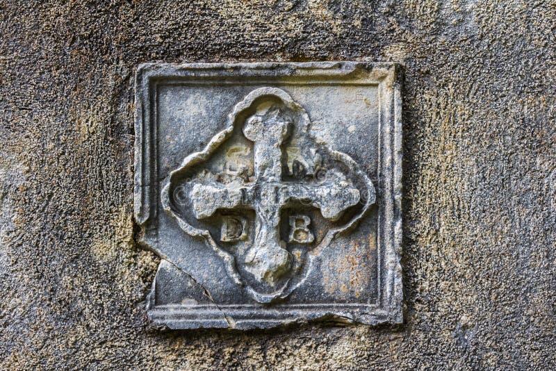 Forntida basrelief i form av ett kristet kors på den kyrkliga väggen arkivbilder