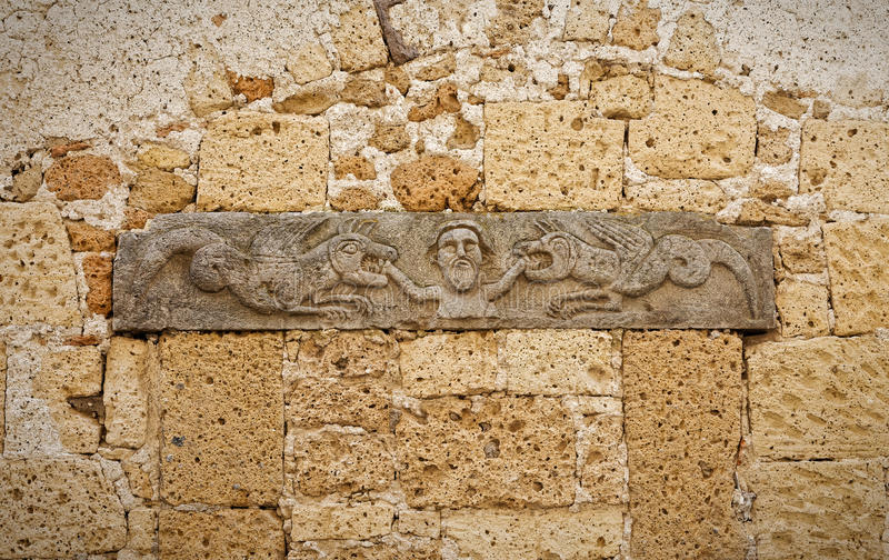 Forntida basrelief på en vägg av tuffen som föreställer en biten man arkivbilder
