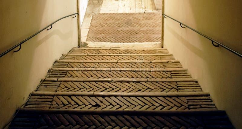 Forntida belagd med tegel trappuppgång med järnledstången arkivfoton