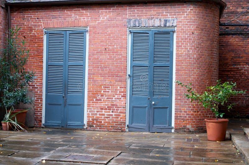 Forntida blå dörr i en tegelstenvägg arkivfoto