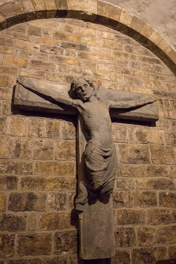 Forntida bruten staty av Jesus Christ på väggen Medeltida stena korset i medeltida kyrka Forntida kryptagarnering royaltyfri fotografi