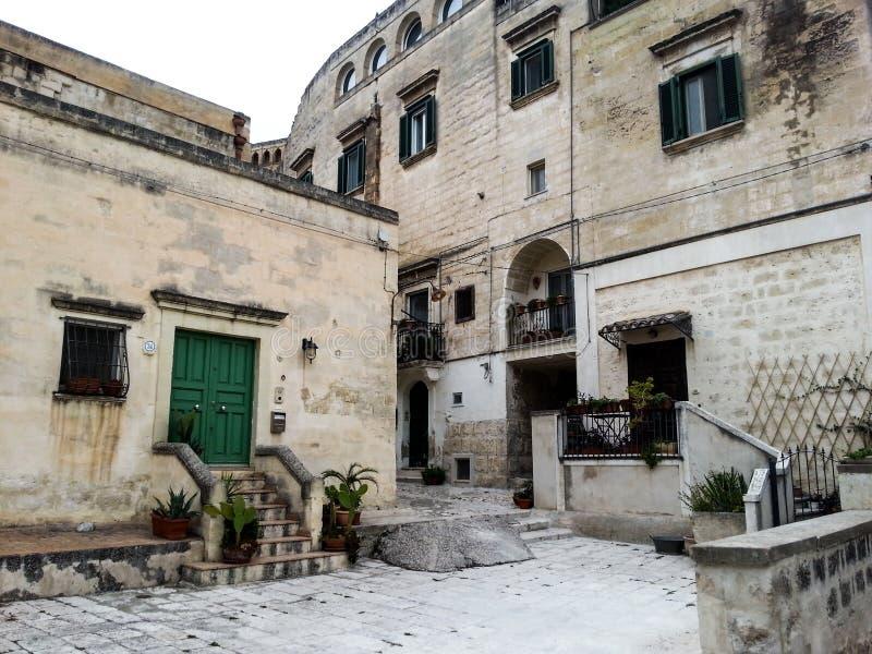 Forntida byggnader med gröna slutare och dörrar till staden av Matera arkivbilder