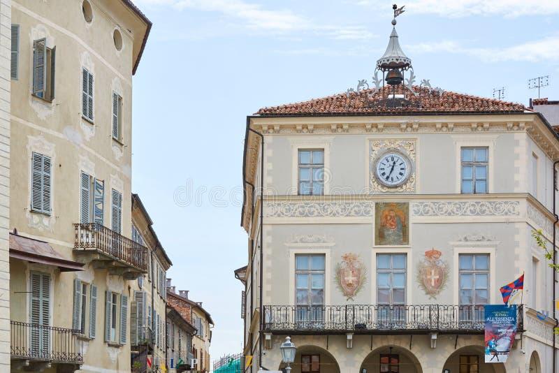Forntida byggnader med klockan, freskomålningar och klocka i en sommardag, blå himmel i Mondovi, Italien royaltyfria foton