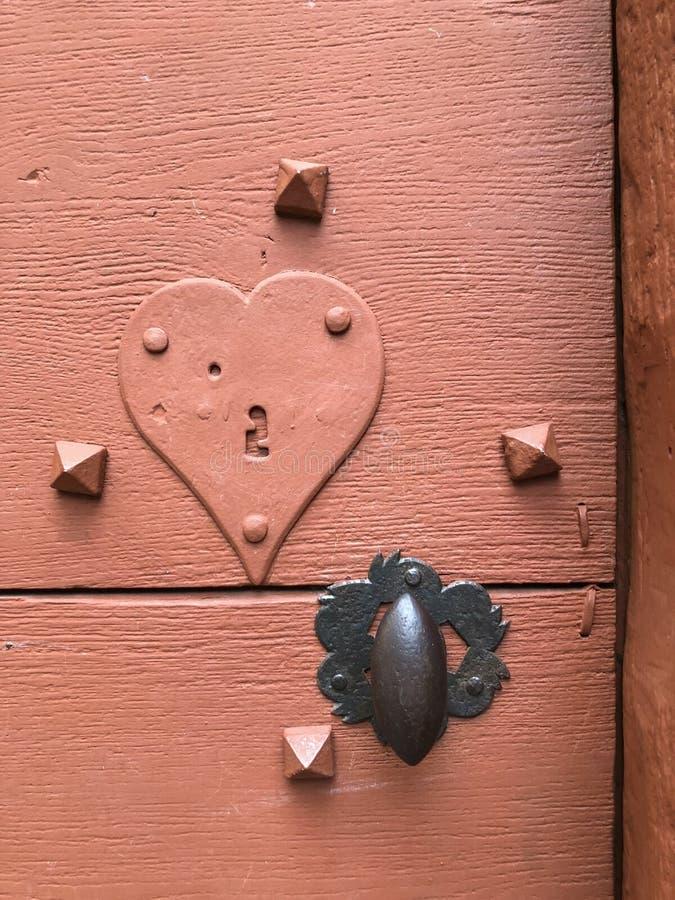 Forntida dörr med låsnyckelhålet med en hjärta arkivbilder