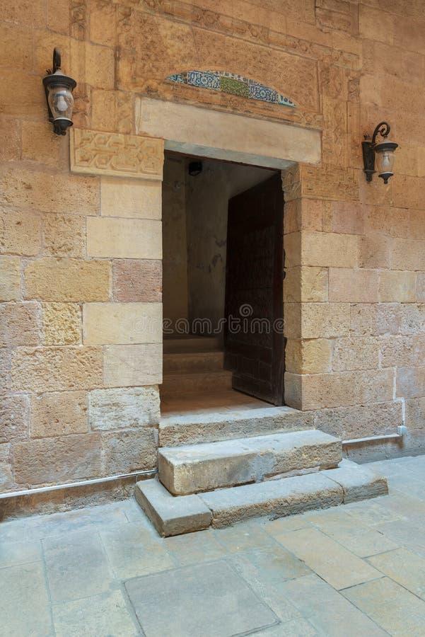 Forntida dekorerad tegelstenstenvägg och dörröppning som leder till huset av historisk byggnad för egyptisk arkitektur, Kairo, Eg arkivbild