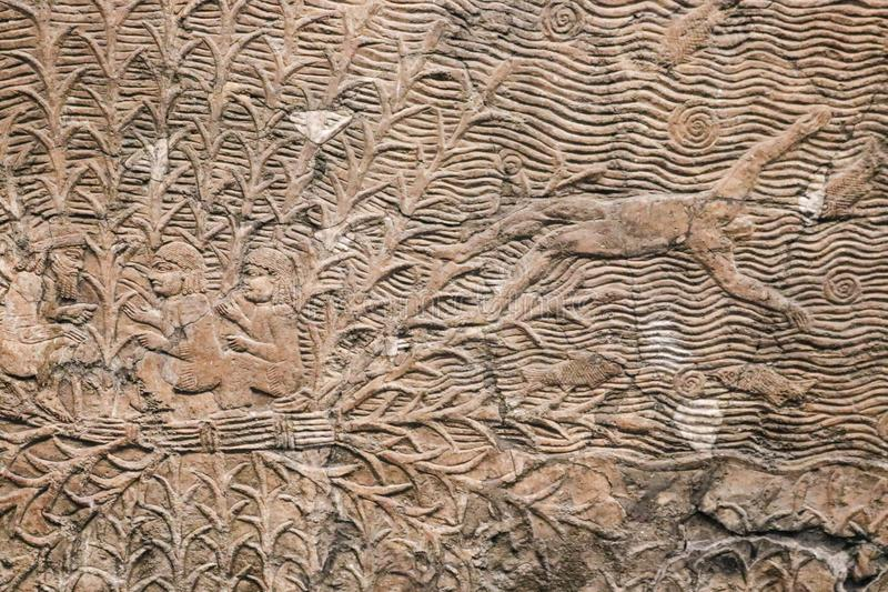 Forntida egyptisk stenpanel med att snida för lättnad av mannen som kastas ut ur ett fartyg in i havet med fiskar - bakgrund arkivfoton