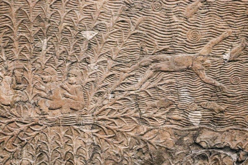 Forntida egyptisk stenpanel med att snida för lättnad av mannen som kastas ut ur ett fartyg in i havet med fiskar - bakgrund royaltyfri fotografi