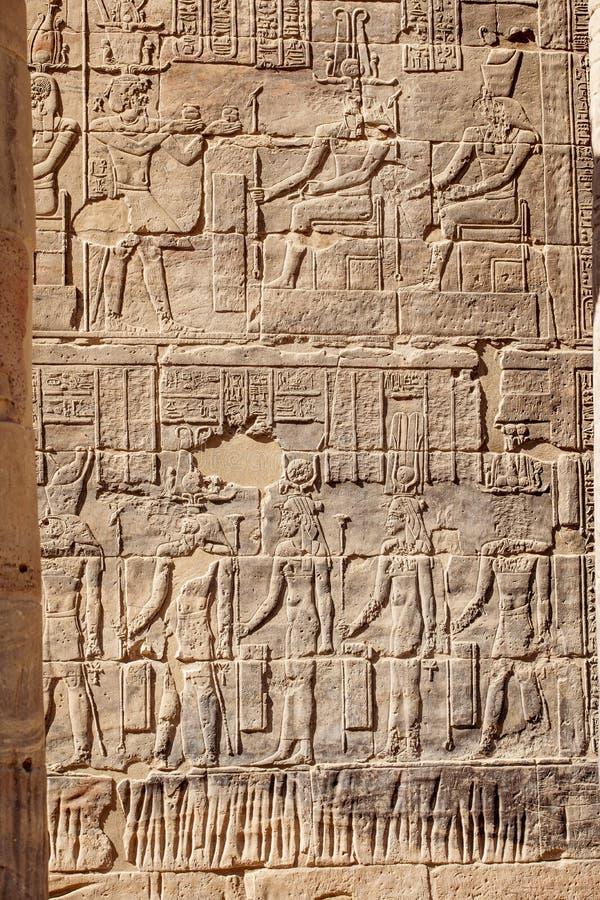 Forntida egyptiska hieroglyf som snidas i sten på den Philae templet i Aswan Egypten royaltyfri fotografi