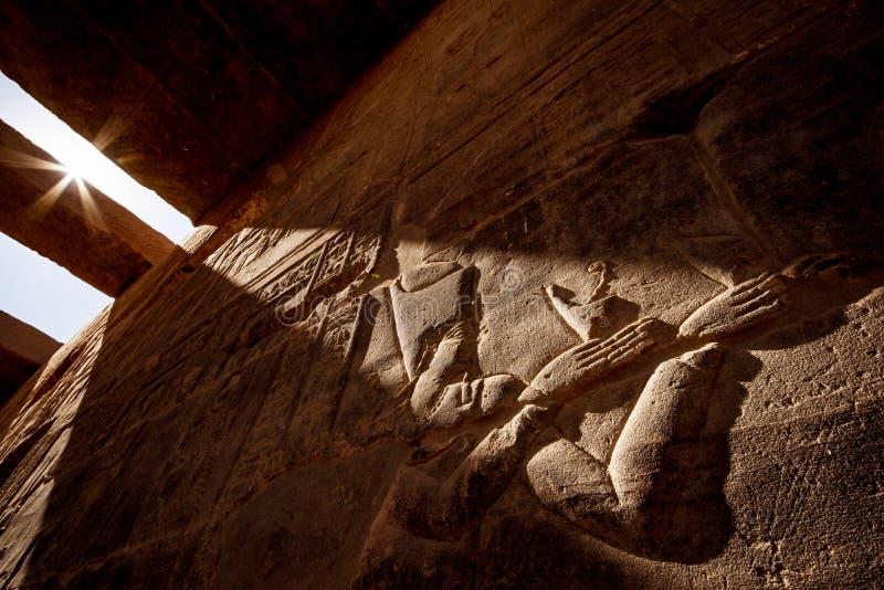 Forntida egyptiska hyeroglyphs i solnedgångljus på den Aswan templet Philae i Egypten fotografering för bildbyråer