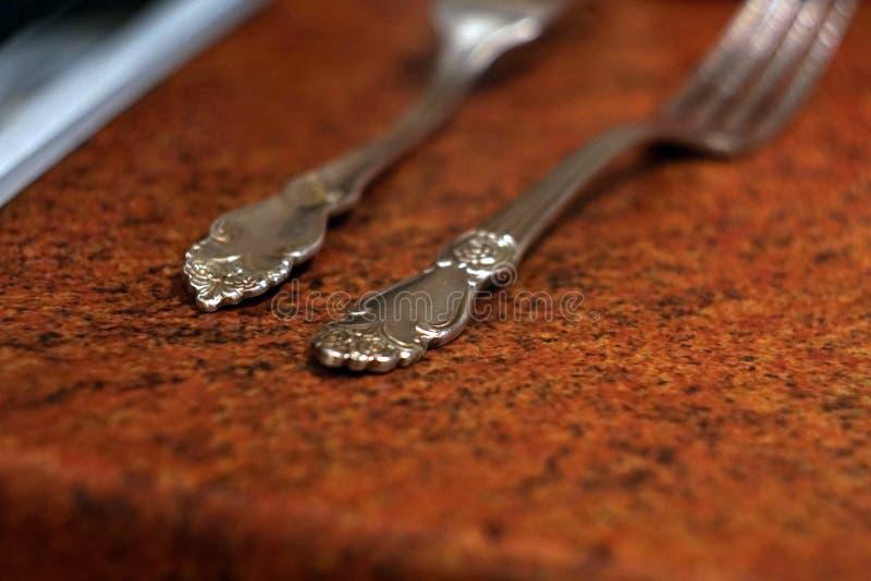 Forntida försilvra gaffelhandtag på ett kök royaltyfri foto