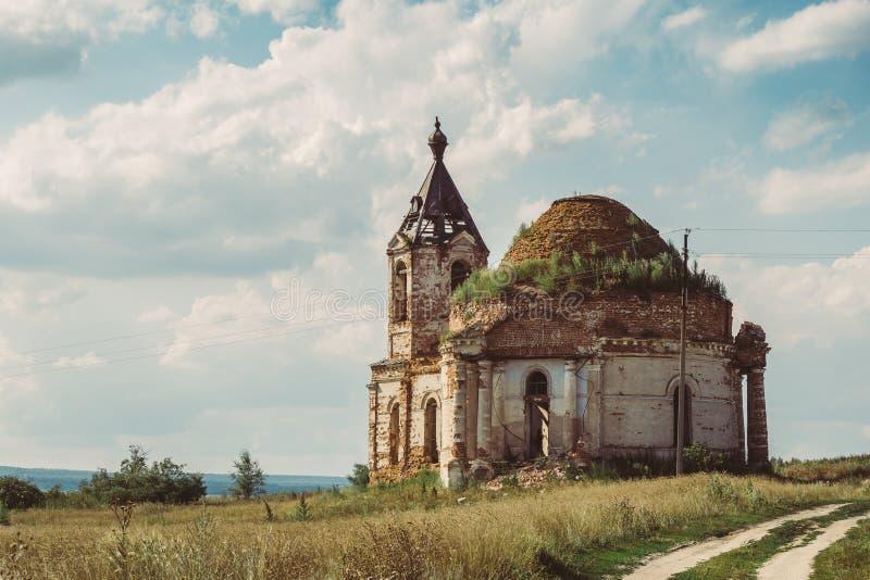 Forntida förstörd rysskyrka eller tempel som är bevuxna med gräs bland fält royaltyfri bild