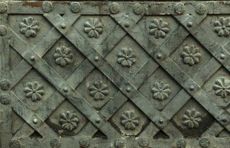 Forntida falsk metalltextur med dekorativa samkopieringar Dörrar portar, slutare Detalj av en medeltida grå dörr med metalldecora royaltyfria bilder
