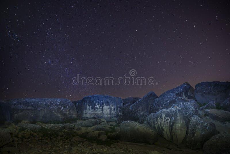 Forntida hällristningar under stjärnorna i natten royaltyfri bild
