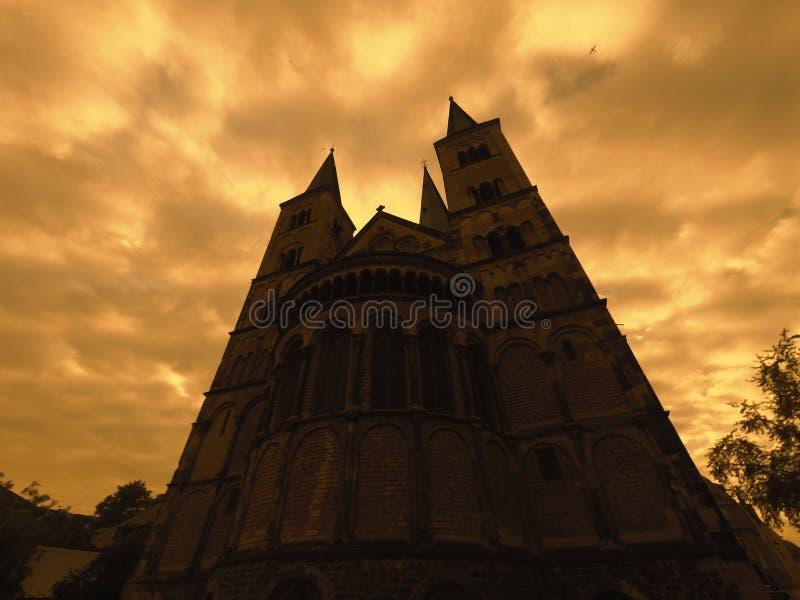 Forntida katolsk kyrka under molniga skyes, tappningfärgfasa som ser plats arkivfoton
