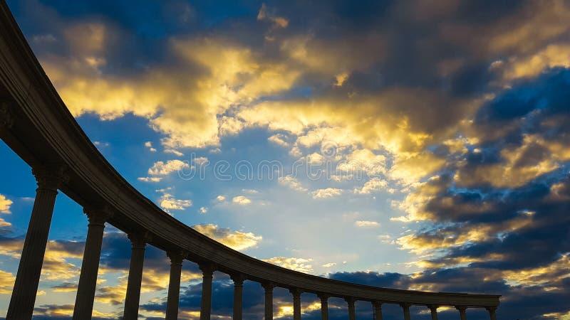 Forntida kolonnkontur på himmel för inställningssol royaltyfri foto