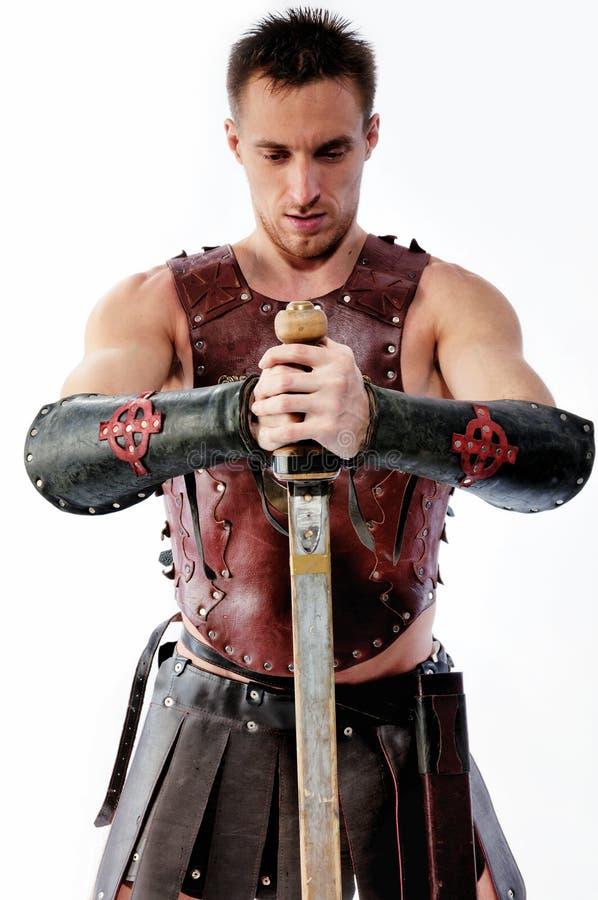 Forntida krigare med svärdet på vit bakgrund arkivfoto