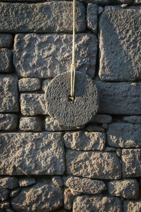 Forntida kvarnsten på väggen arkivbilder