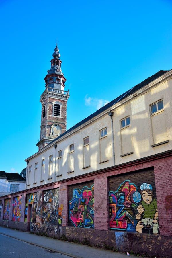 forntida kyrkligt torn i återställande och modern gatakonst på en yttre vägg arkivbilder