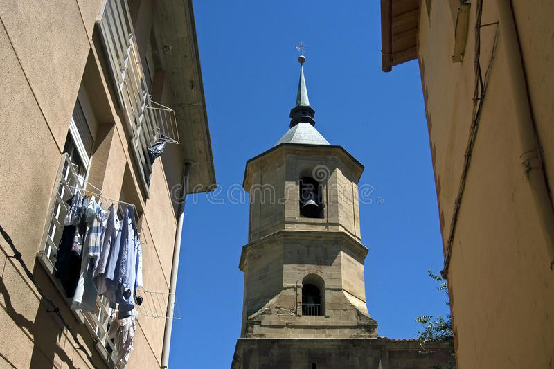 Forntida kyrkligt torn mellan hus, Spanien arkivfoto