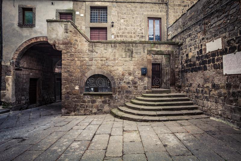 Forntida medeltida hus I tegelsten och sten, yttre del med ingången och trappa arkivfoton