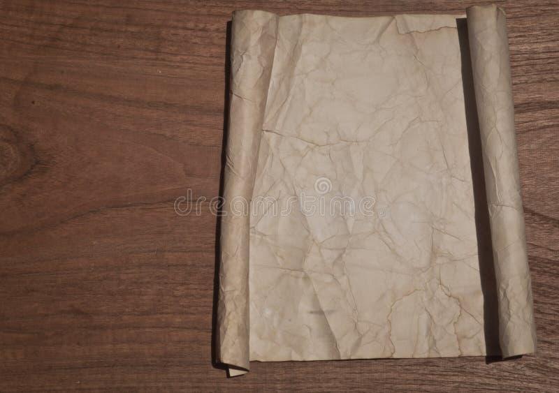 Forntida skrynklig pappers- snirkel på den wood tabellen för bakgrund arkivfoto
