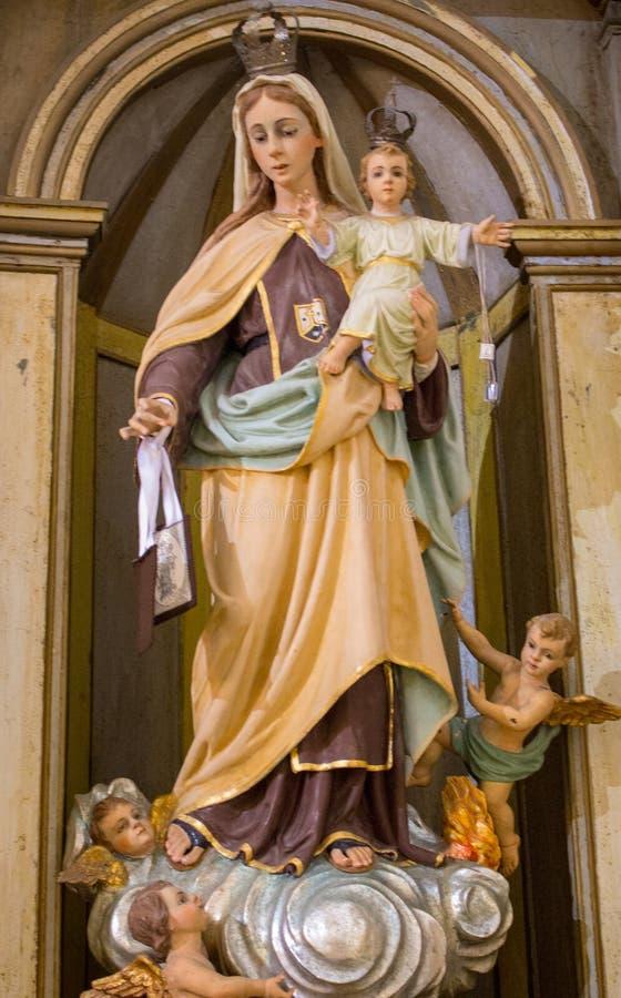 Forntida skulptur av oskulden Mary med Jesus och änglar Tappningstatyn av modern av guden och Jesus Christ behandla som ett barn arkivfoton