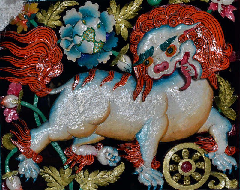 Forntida skulptur med en bild av ett vitt snölejon med en orange man och smaragdögon, symbol av buddism och Tibet arkivbild