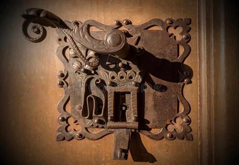Forntida smidesjärnlås av en dörr med nyckelhål arkivbild