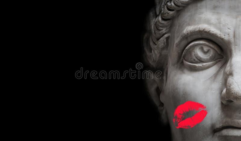 Forntida staty av kraftiga Roman Nobel Man med det röda läppstifttrycket på hans kind som isoleras på svart bakgrund, urspårninga arkivbilder