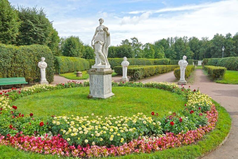 Forntida statyer i blommaträdgården arkivfoto