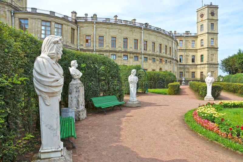 Forntida statyer i trädgården bredvid slott arkivfoton